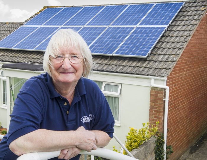 Image of happy customer in front of house with solar panels on