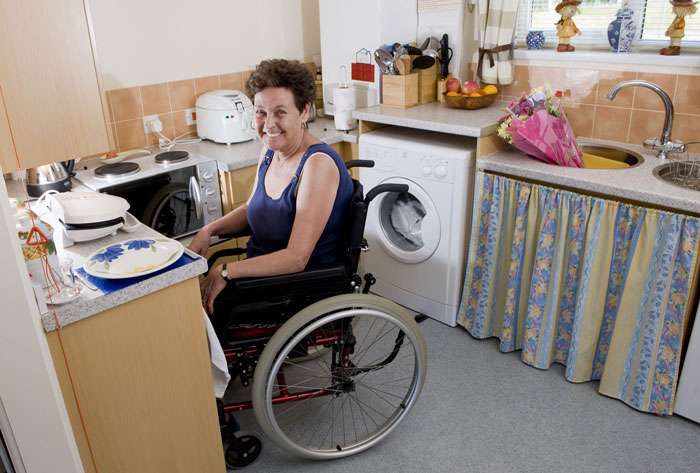 Female resident in wheelchair shown enjoying newly adapted kitchen